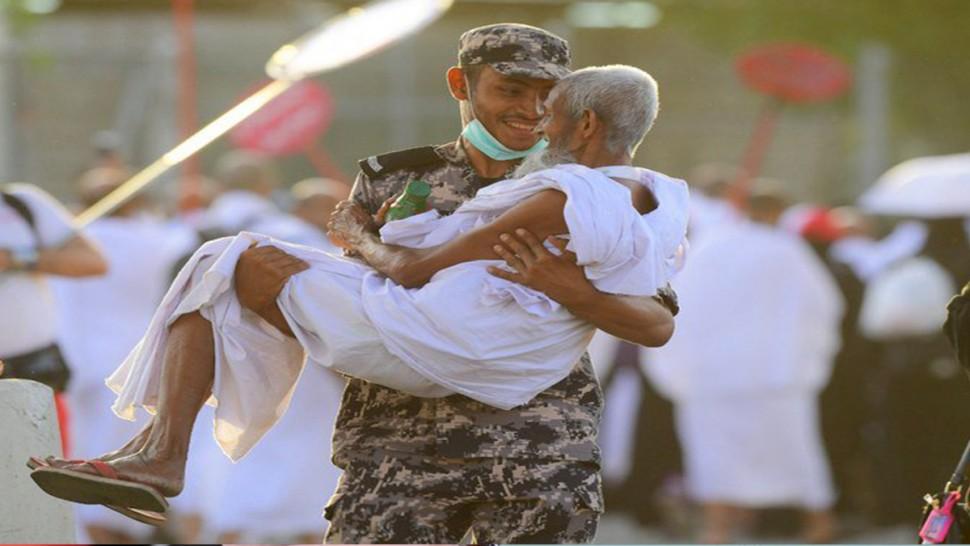 رجل امن سعودي يحمل حاجا